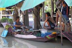 人乘小船运载食物 免版税库存图片
