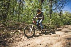 年轻人乘驾登山车通过森林 库存图片