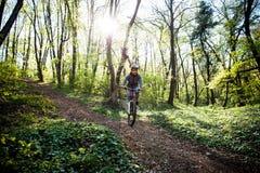 人乘驾登山车通过森林 图库摄影