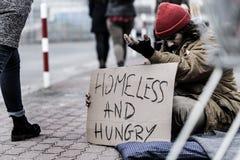 人乞求在拥挤的街上 库存图片