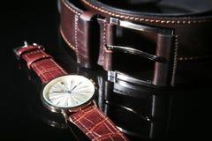 人事务和rekreation的` s辅助部件 皮带、手表、笔记薄和笔在黑镜子背景 顶视图 免版税库存照片