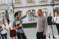 人二 招呼 五高 照相机组查出查找关于常设工作室空白年轻人的人 免版税库存图片