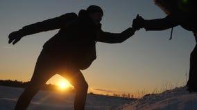 人互相帮助通过握手和舒展冠上征服高多雪的山山顶在 股票视频