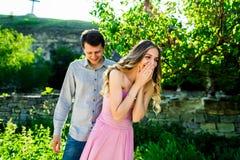 年轻人亲吻的夫妇在与摇摆的大树下 免版税库存照片