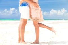 年轻人亲吻的夫妇的腿在热带绿松石的 免版税库存照片