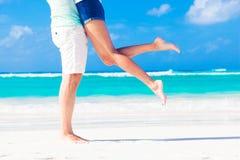 年轻人亲吻的夫妇的腿在热带绿松石的 库存照片