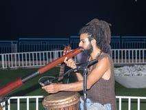 年轻人人在江边的晚上播放一个大管子在市纳哈里亚,在以色列 库存照片