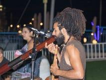 年轻人人在江边的晚上播放一个大管子在市纳哈里亚,在以色列 免版税图库摄影