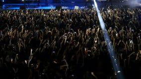 人人群摇滚乐音乐会的 爱好者在摇滚乐队的表现前面会集 股票视频