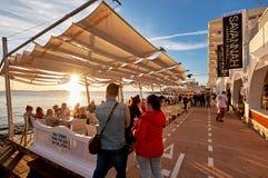 人人群遇见日落在大草原咖啡馆沿海岸区大阳台  免版税库存照片