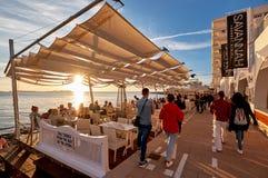 人人群遇见日落在大草原咖啡馆沿海岸区大阳台  免版税库存图片