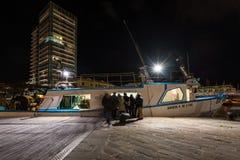 人从一条小船的购买鱼在萨沃纳,意大利 库存照片