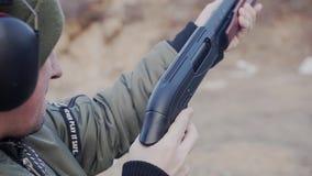 人从大口径猎枪射击,并且,在射击做再充电后