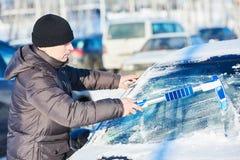 人从雪的清洁汽车 免版税库存照片