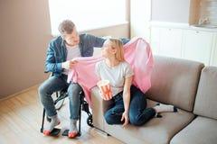 人以伤残和包括照顾女朋友 他在她的肩膀上坐轮椅和把毯子放 库存照片