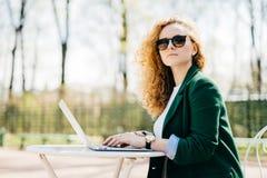 人们、休闲、技术和通信 美丽的女实业家佩带的太阳镜和典雅的夹克使用便携式计算机 免版税库存照片