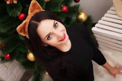 人们、假日和魅力概念-晚礼服的微笑的妇女在圣诞树 免版税库存照片