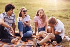 人们、友谊和乐趣 四个人和妇女朋友度过室外的周末,嘲笑滑稽可笑的故事,有快乐的表示,坐 库存照片