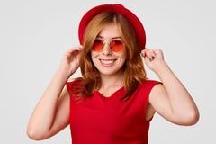 人们、样式和衣物概念 红色帽子、树荫和T恤杉的愉快的逗人喜爱的年轻女性,是高兴为烦恼被拍摄 图库摄影
