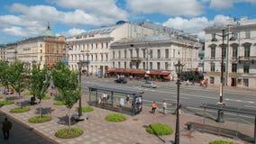 人们、汽车和城市公共汽车在涅夫斯基街道上在夏天 免版税库存照片