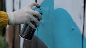人们、艺术、创造性和青年文化概念-接近手与喷漆的图画街道画在街道墙壁上 库存照片