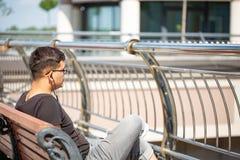 人们、音乐、技术、休闲和生活方式-有耳机的行家人听到在城市街道长凳的音乐的 免版税库存照片
