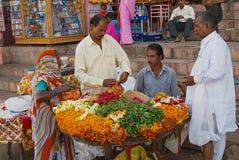 人们为宗教目的卖花在河沿在瓦腊纳西,印度 库存图片