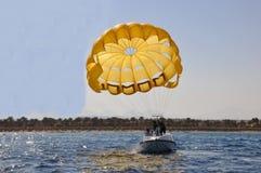 人们乘坐有降伞的一条小船 免版税库存照片