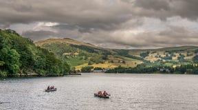 人们乘独木舟在湖的,上面暴风云 库存图片