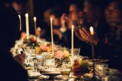 人们享受与蜡烛的一顿家庭晚餐 大桌服务用食物和饮料 免版税库存图片