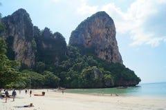 人们享用天空蔚蓝和绿松石海滩的和岩石在甲米府,泰国 免版税库存照片