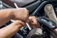 人们修理摩托车用途板钳和螺丝刀工作 图库摄影