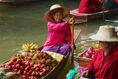 人们卖从小船的食物在浮动市场上在Damnoen Saduak,泰国 图库摄影