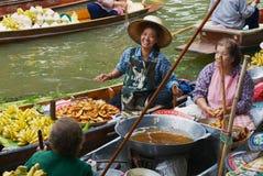 人们卖从小船的食物在浮动市场上在Damnoen Saduak,泰国 库存图片