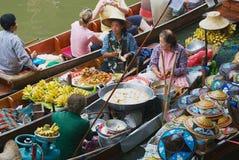 人们卖从小船的食物在浮动市场上在Damnoen Saduak,泰国 免版税库存图片
