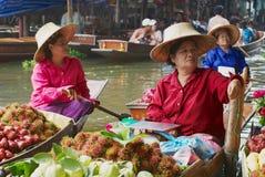 人们卖从小船的食物在浮动市场上在Damnoen Saduak,泰国 免版税库存照片