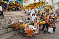 人们卖花给香客在圣洁恒河银行在瓦腊纳西,印度 免版税库存照片