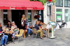 人们吃饮料咖啡馆餐馆室外大阳台, Jordaan阿姆斯特丹,荷兰 免版税库存照片