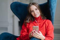 人们和技术概念 满意的女性meloman享受喜爱的音乐,听音频纪录,穿戴在红色毛线衣,海浪 库存图片