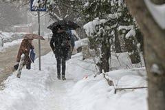 """人们在一条非常多雪的边路走在暴风雪期间在市索非亚,保加利亚†""""2月26,2018 免版税库存图片"""