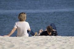 人们在与饮料的海滩放松 免版税库存照片