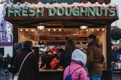 人们在冬天妙境圣诞节市场的一个报亭买新鲜的多福饼在伦敦,英国 库存照片