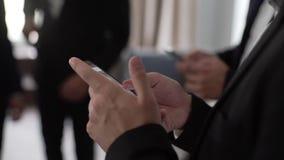 人们在古典黑衣服供以人员使用手机和智能手机户内 股票录像