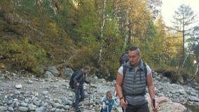 人们在山河附近走 家庭旅行 由山,河,小河的人环境 父项和孩子 股票录像
