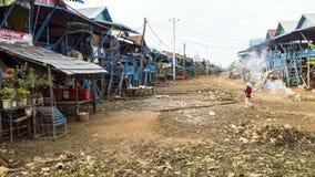 人们在恶劣的浮动村庄崇公Knies在柬埔寨, Tonle Sap伟大的湖 狗 免版税库存照片