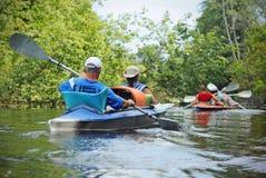 人们在河乘独木舟 免版税库存图片