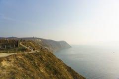 人们在沿黑海的陡峭的海岸的路走在一有雾的秋天天 阿纳帕度假村的周围  免版税图库摄影