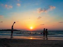 人们在海滩上有效地花费时间在日落 库存图片