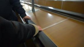 人们在自动扶梯,在栏杆的人的手移动 影视素材
