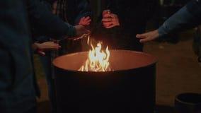 人们在街道上的火旁边温暖手 影视素材